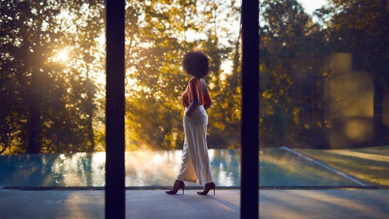 Blick durch bodentiefe Fenster auf Frau, die an Pool steht