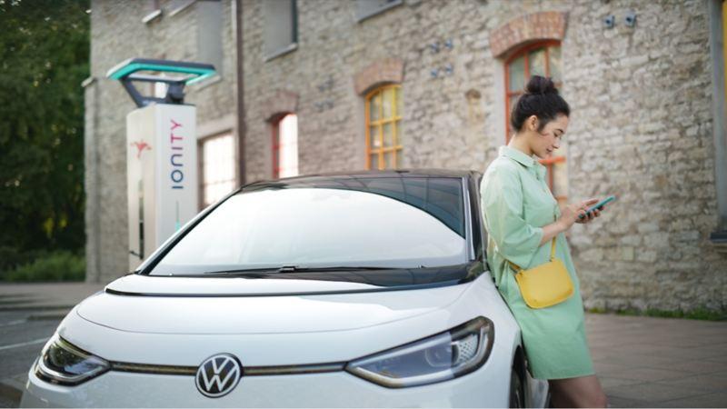En kvinne lener seg til elbilen VW Volkswagen ID.3 ved en IONITY hurtigladestasjon