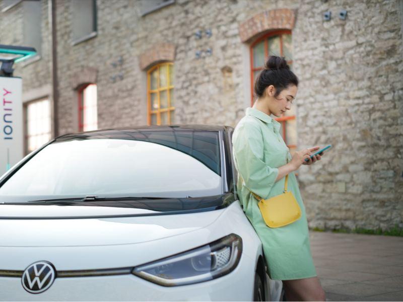 En kvinne står ved siden av VW Volkswagen ID.3 elbil mens den lader på IONITY lynladestasjon
