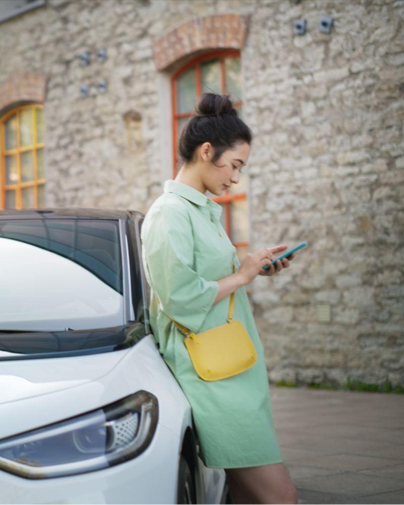 Eine Frau lehnt am VW ID.3, während das Fahrzeug an einer IONITY-Ladesäule läd.