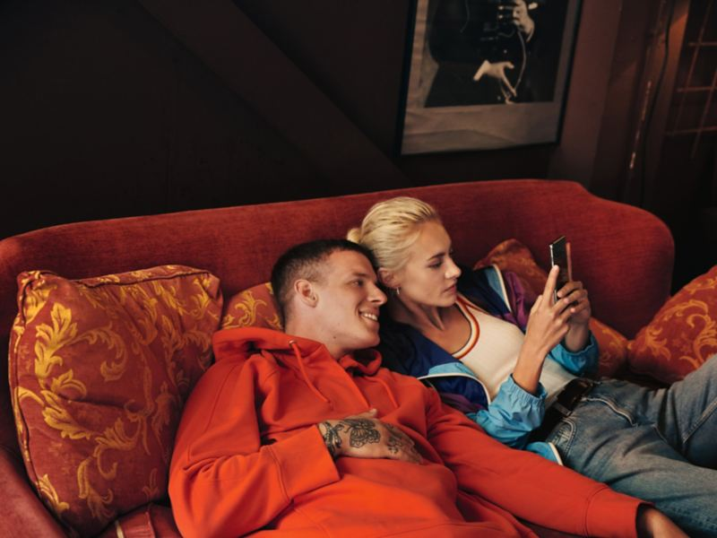 Couple relaxing on a couch and looking at a smartphone