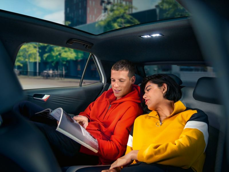 Two young adults read on the backseat of the ID.3