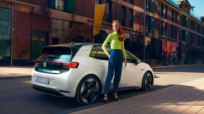 VW ID.3 schräge Heckansicht, Frau steht neben dem Auto