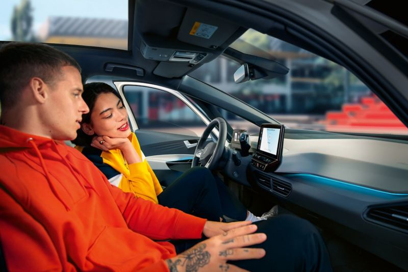 People in the front seat of the Volkswagen ID.3 looking at the radio display.