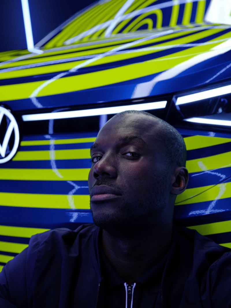 A man sitting in front of a camouflaged all-electric Volkswagen ID.4