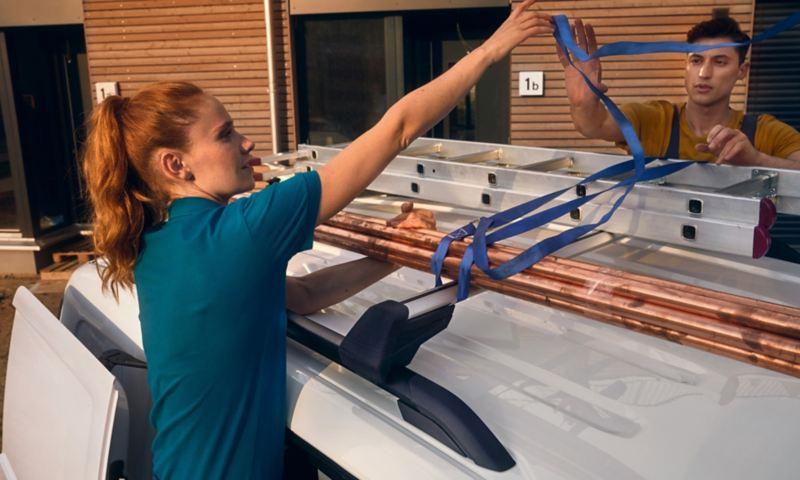 Een vrouw en een man bevestigen een ladder op het dak van de nieuwe Volkswagen Caddy Cargo.