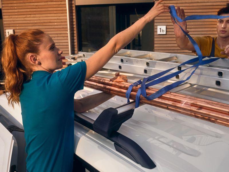 Une femme et un homme attachent une échelle sur le toit de la nouvelle Volkswagen Caddy Cargo.