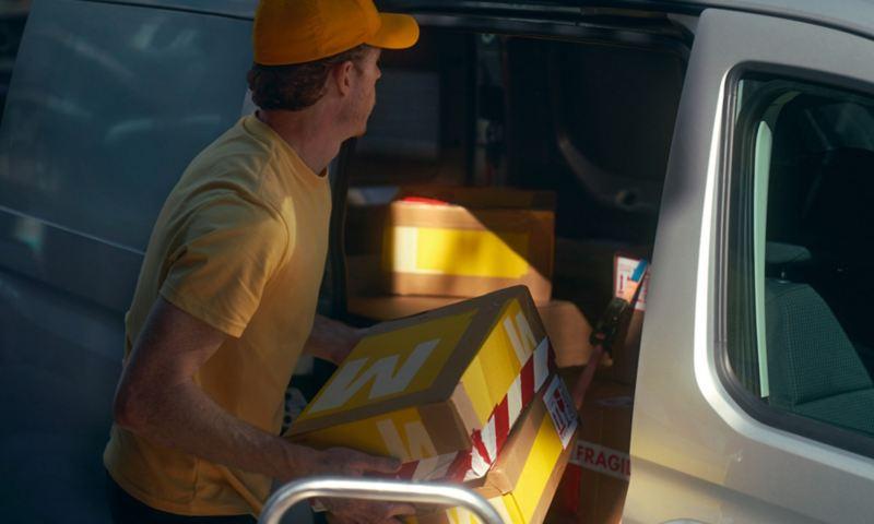 Een man laadt de nieuwe Volkswagen Caddy Cargo vol met pakketten.