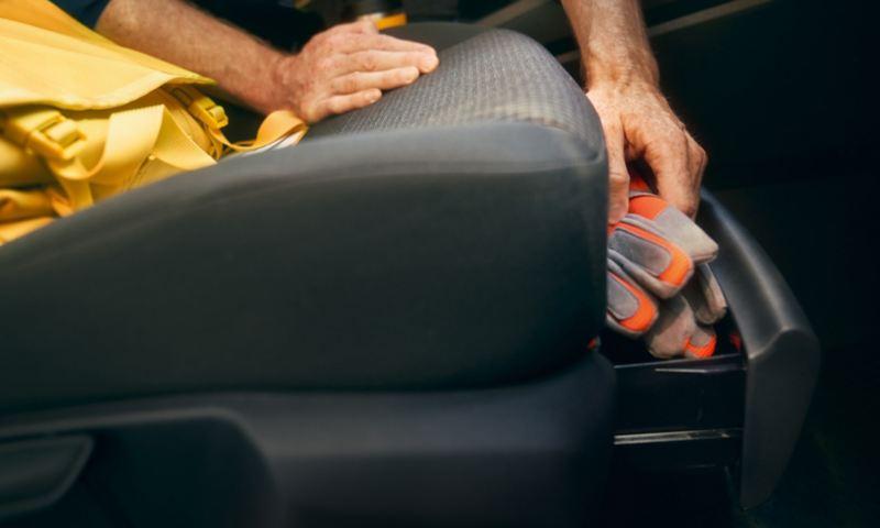 Un homme prend une paire de gants dans le tiroir sous le siège du passager avant de la nouvelle Volkswagen Caddy Cargo.