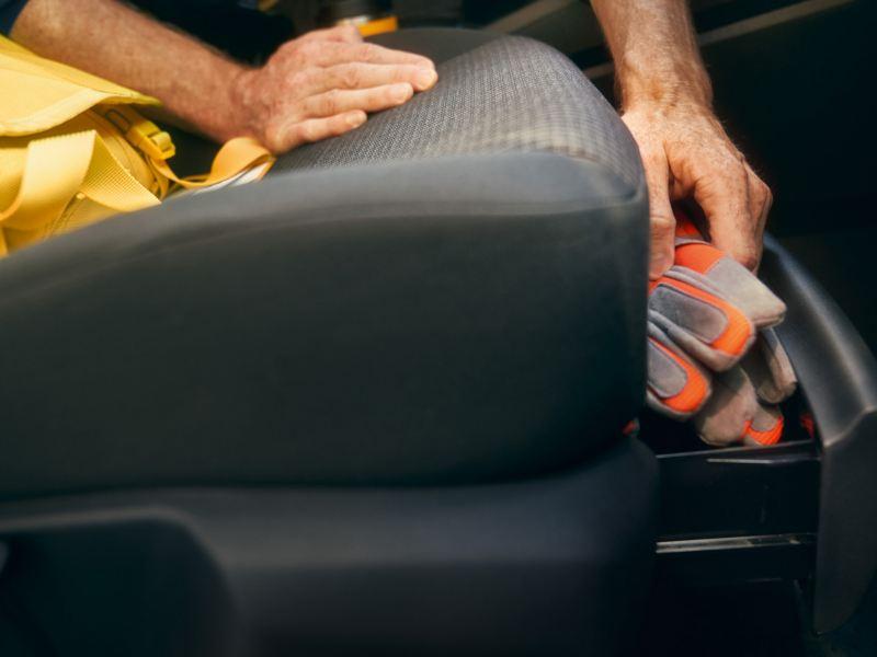 Een man haalt handschoenen uit de lade onder de passagiersstoel vooraan van de nieuwe Volkswagen Caddy Cargo.