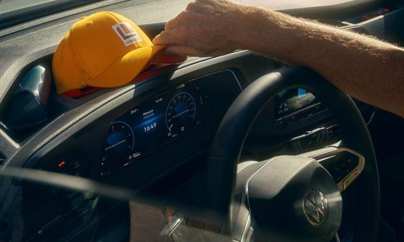 Un homme dépose sa casquette sur le tableau de bord de la nouvelle Volkswagen Caddy Cargo.