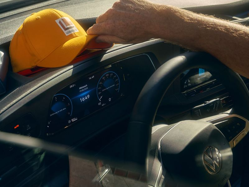 Een man legt zijn pet op het dashboard van de nieuwe Volkswagen Caddy Cargo.