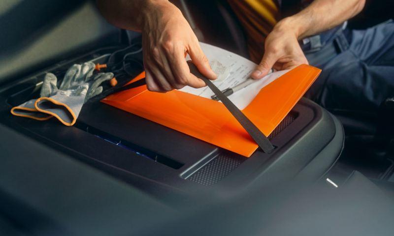 Een man bevestigt een map aan de rugleuning van de passagiersstoel vooraan van de nieuwe Volkswagen Caddy Cargo.