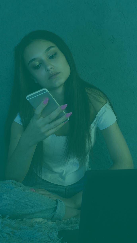 Flicka sitter med sin telefon och dator