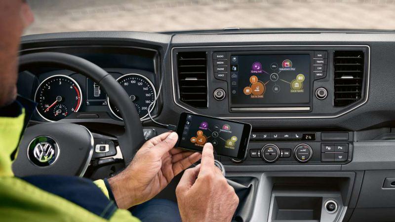 Henkilö käyttää älypuhelimen ja auton yhteistä sovellusta auton sisällä