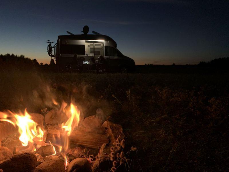 Volkswagen Grand California przy ognisku po zmroku