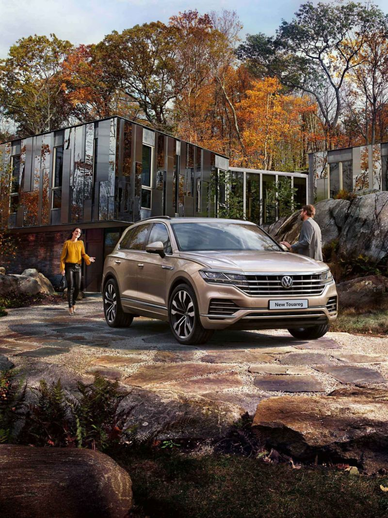 Two adults standing next to a parked Touareg