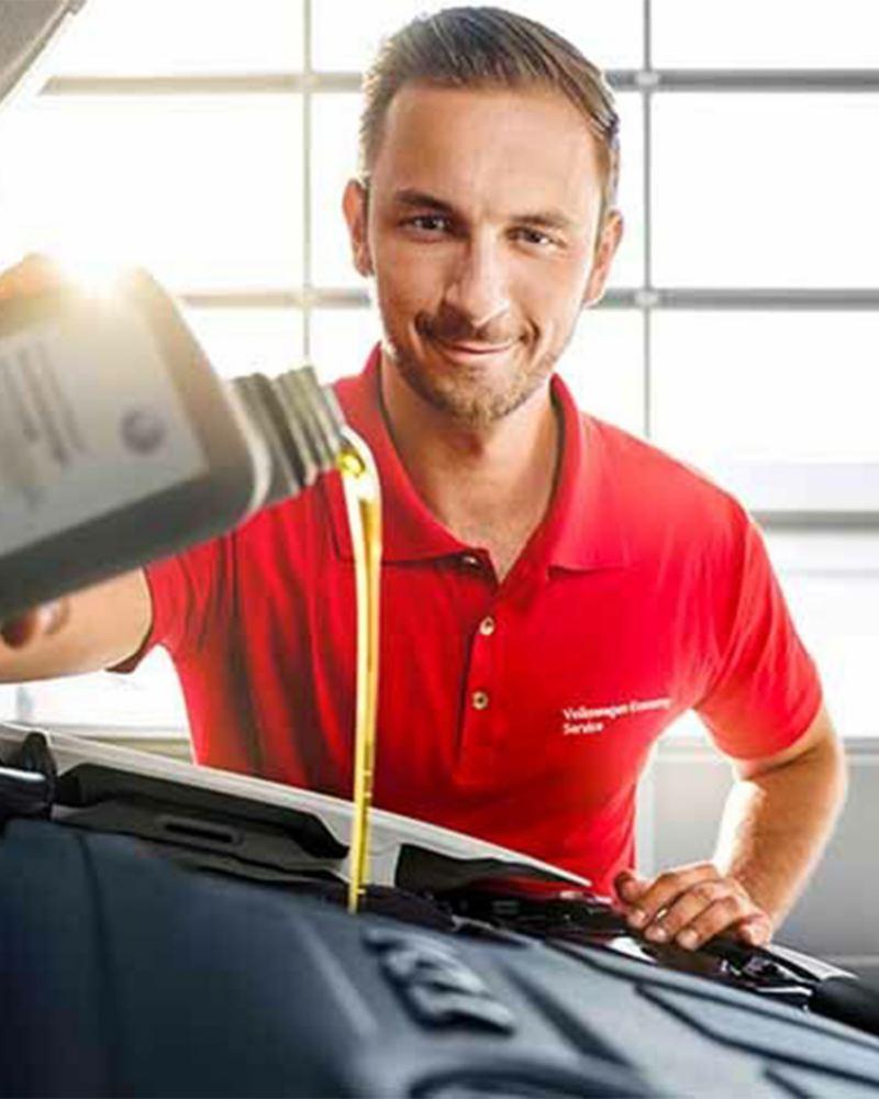 Kfz-Mechaniker füllt Öl nach