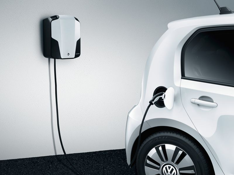 A white Volkswagen e-up! charging, using a wall mounted charge point.