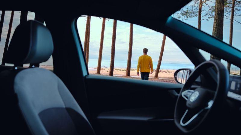 Vista hacia afuera desde un Volkswagen ID. 3 de un hombre junto al mar