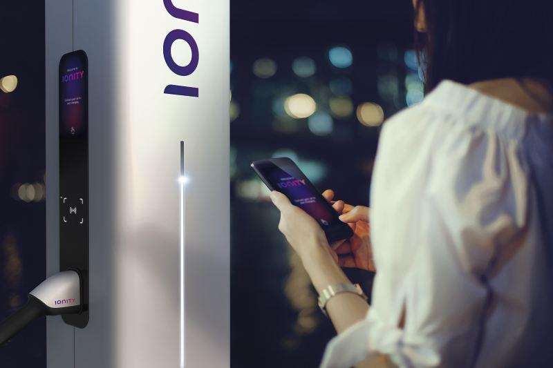 Eine Frau steht mit Smartphone in der Hand von einer Ladesäule von IONITY