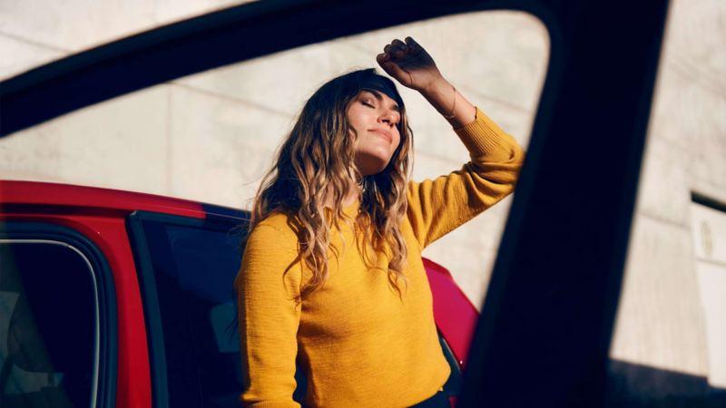Kvinna som står i solen vid en Volkswagen och har ansiktet vänt mot solen och håller handen framför ansiktet för att inte bli bländad