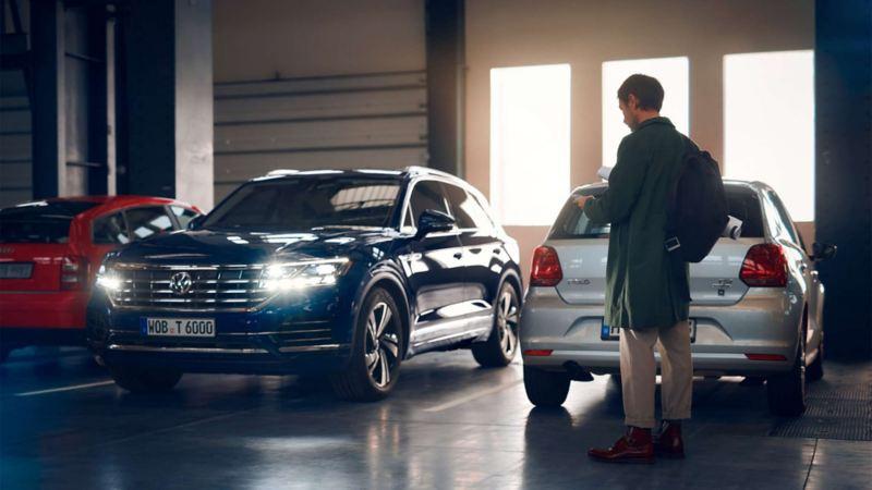 Man står på parkering vid sin Volkswagen och manövrerar bilen med mobilen