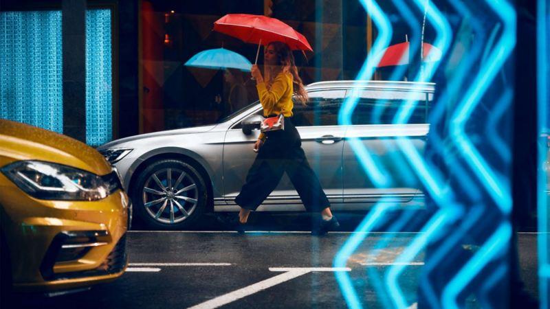 Kvinna med rött paraply går på en väg. Volkswagen bil syns i bild.