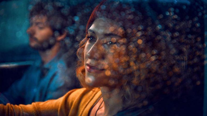 Kvinna och man sitter i en bil. Kvinnan på förarsidan kollar ut genom fönstret som är täckt med regndroppar.