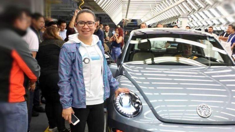 Isabel Jaramillo parada al costado de un Volkswagen Beetle color gris