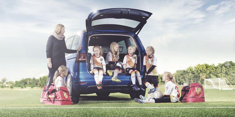 Volkswagen auto kuvattuna takaapäin, auton takaluukku on auki ja siinä istuu useampi jalkapalloa harrastava lapsi. Auton vierellä on lapsia ja yksi aikuinen