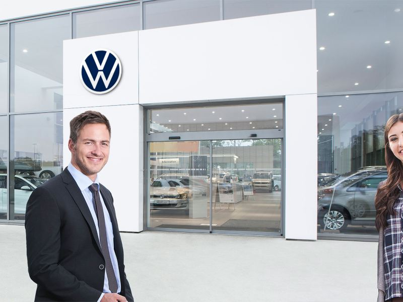 A woman and a man in front of a Volkswagen dealer