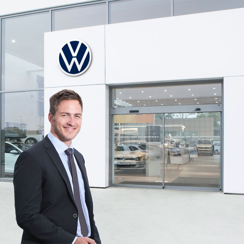 A woman and a man working in front of a dealership