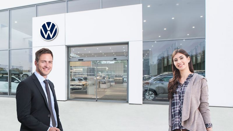 A woman and a man working in front of a Volkswagen dealership