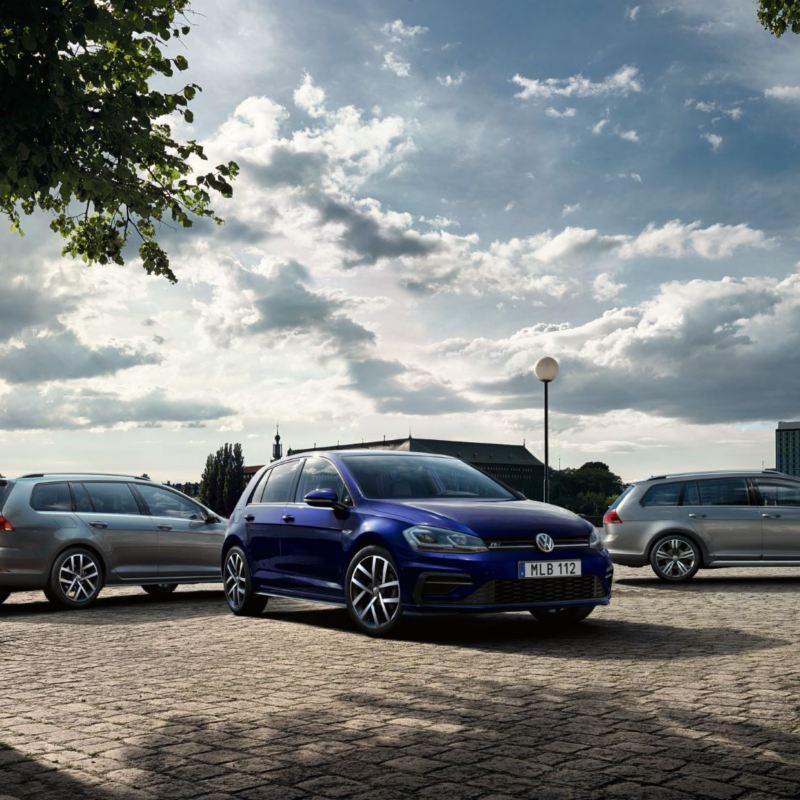 tre Volkswagenbilar parkerade vid vattnet