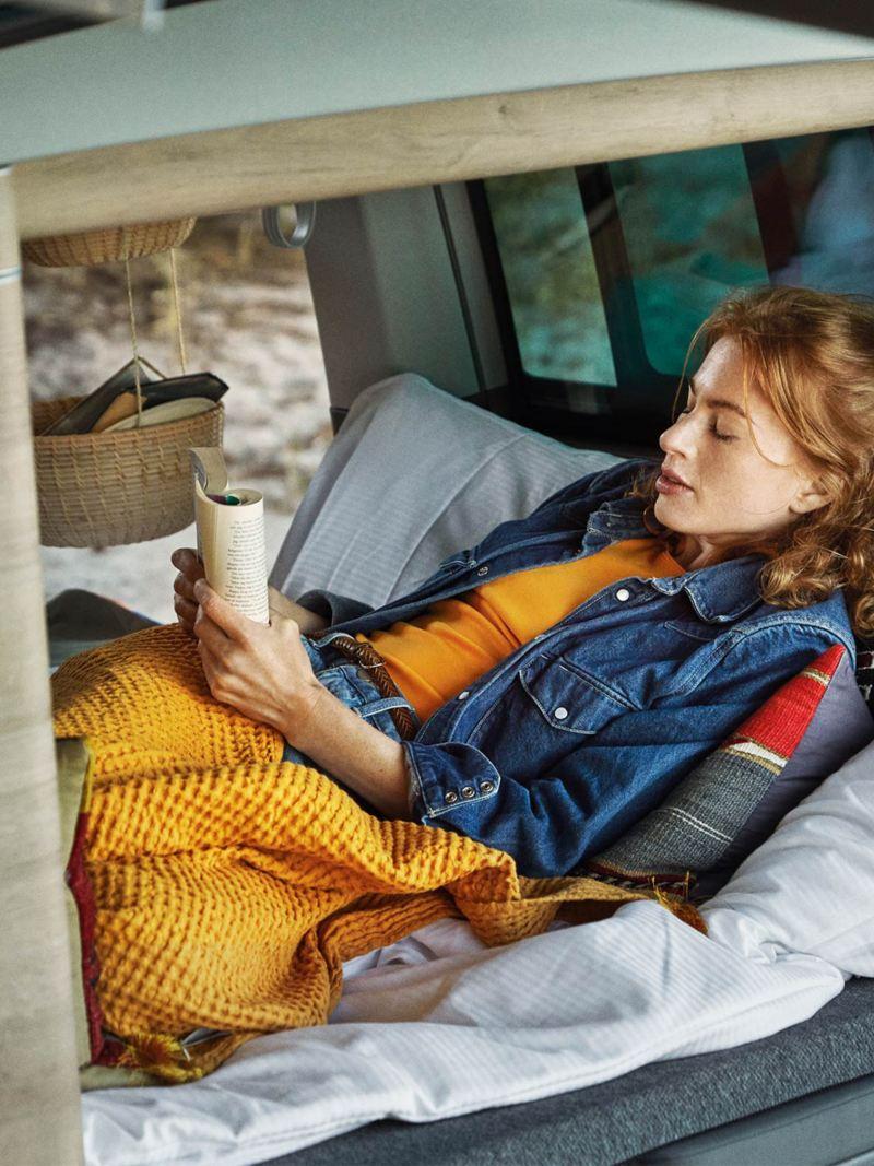 Kvinna läser i en VW California 6.1