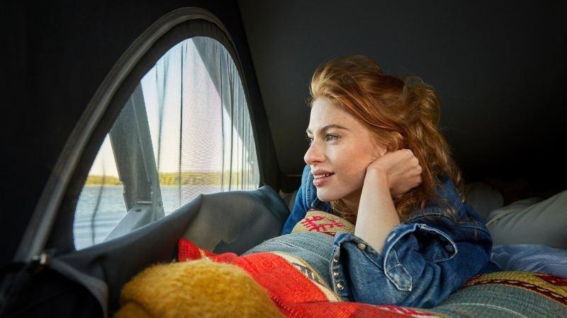 Kvinna i sovloftet på en VW California 6.1