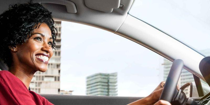 conductrice au volant, immeubles en arrière plan
