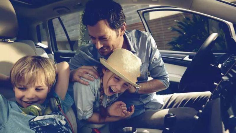 Père avec deux enfants à bord d'un volkswagen