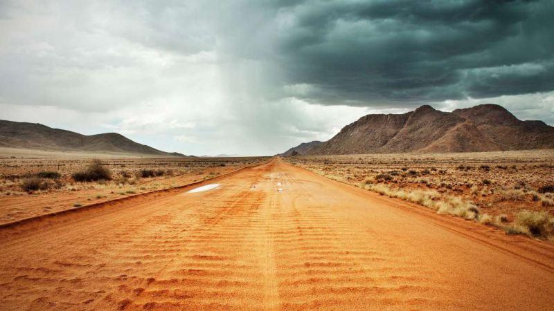vue d'un piste rectiligne, paysage escarpé, montagnes en arrière plan