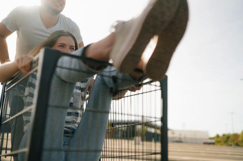 In un parcheggio, un uomo spinge una donna seduta in un carrello per la spesa