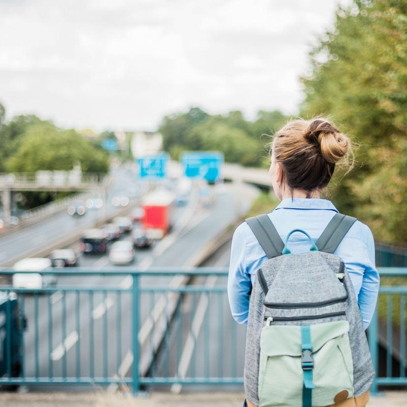 Frau steht auf einer Autobahnbrücke und blickt auf den Verkehr.