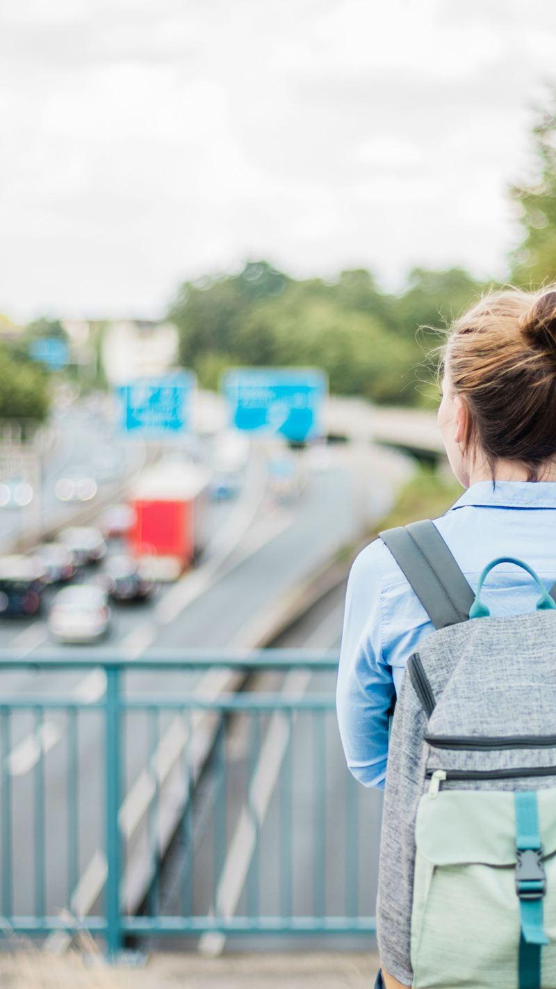 Una donna, in piedi su un ponte sopra l'autostrada, guarda il traffico