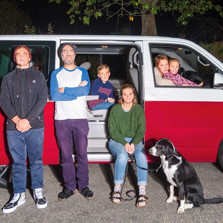 Eine Familie von sechs Personen steht vor einem parkierten Multivan