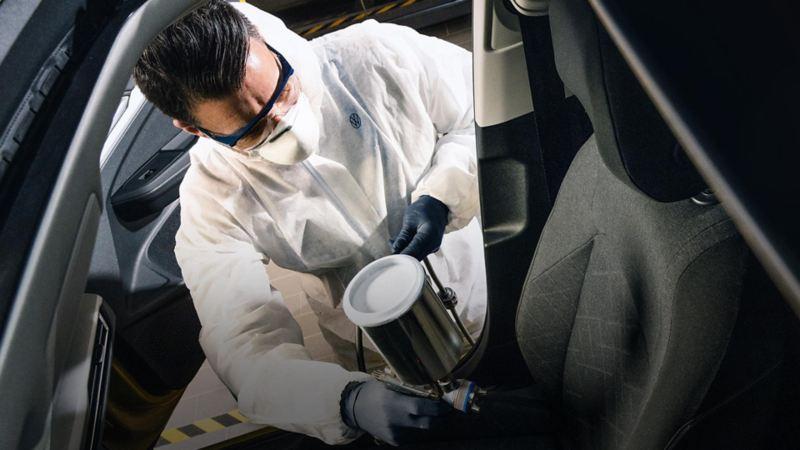 Trabajador VW ofreciendo servicio de limpieza profunda a interior de automóvil Volkswagen
