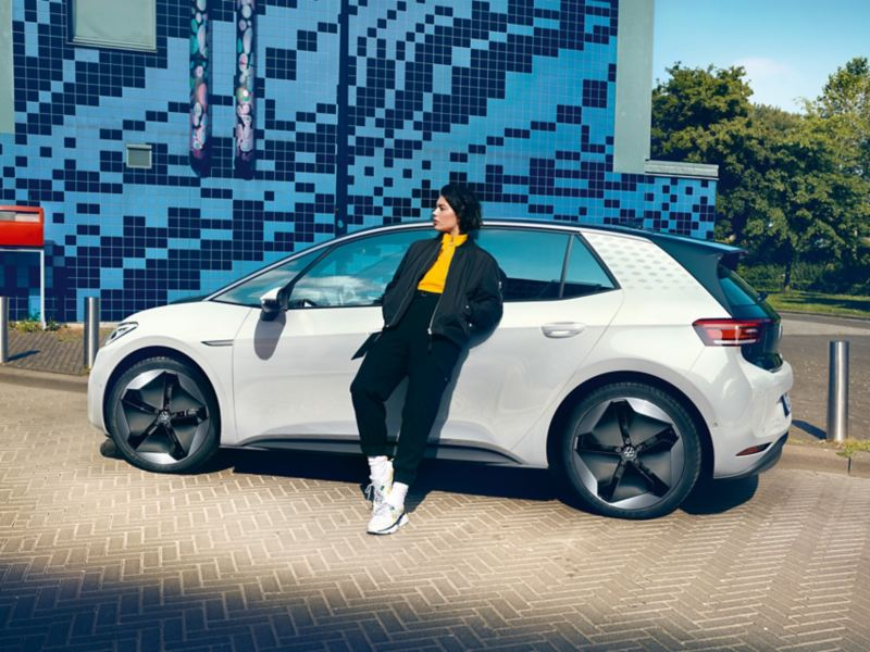 A lady leaning against a white Volkswagen ID. 3 electric car