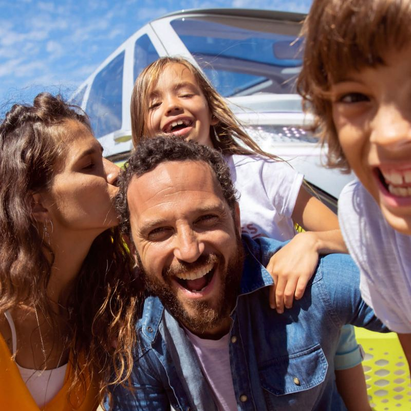 Family enjoying the sun in front of a Volkswagen vehicle