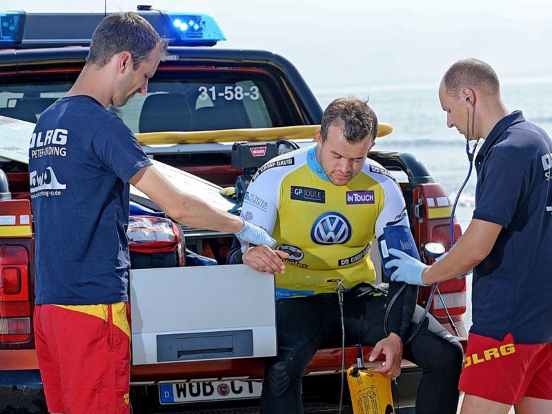 Drei Seenortretter prüfen ihre Ausrüstung am Heck eines Amarok.