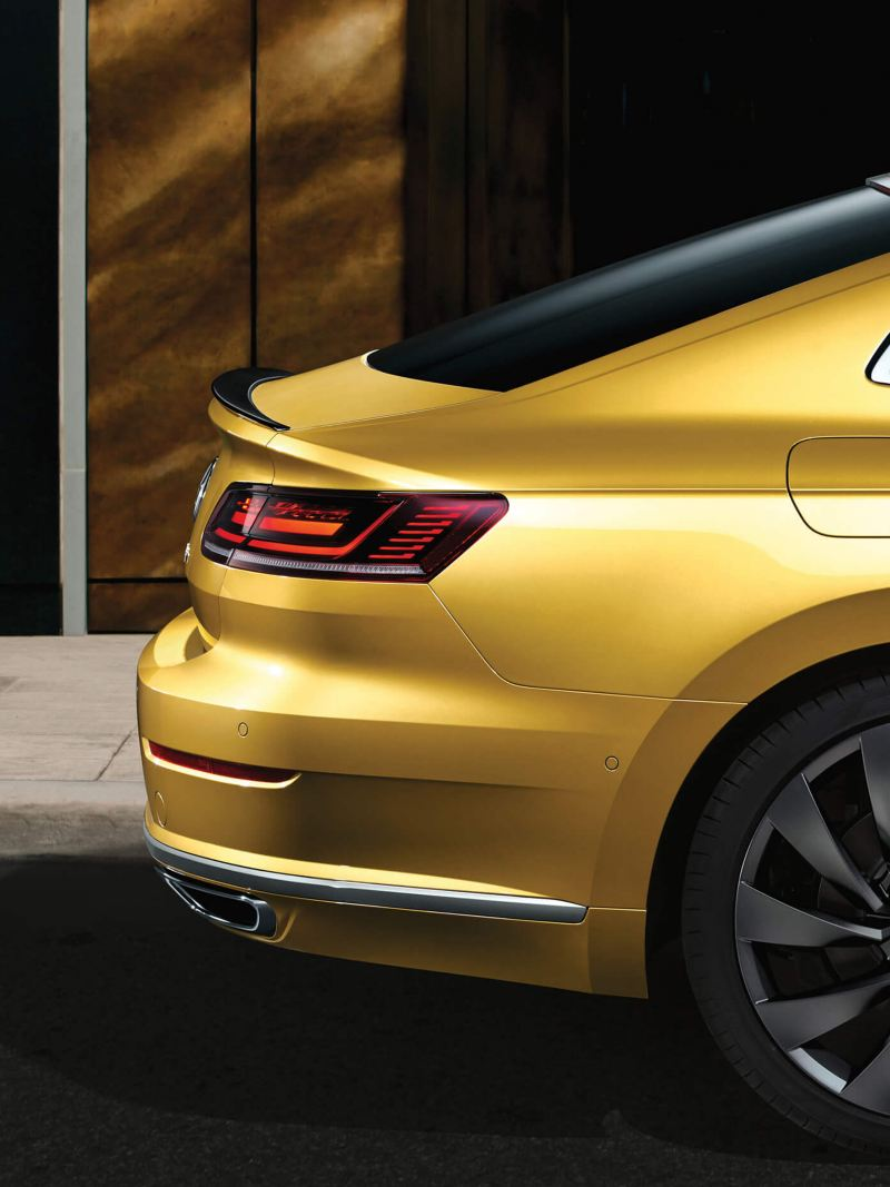 Back focused profile shot of a yellow Volkswagen Arteon, in a city street.