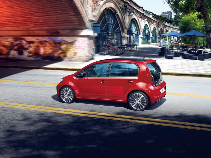 A red Volkswagen up! driving under a bridge.